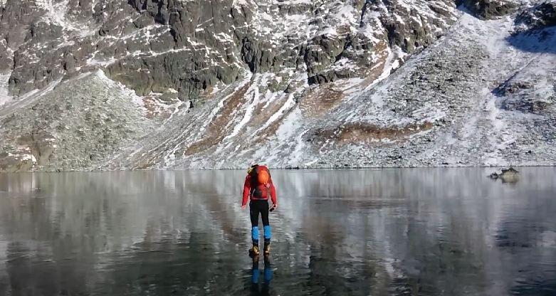 Imaginile care iti taie rasuflarea. Doi alpinisti traverseaza un lac inghetat extrem de limpede - VIDEO