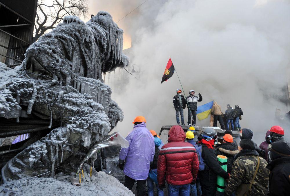 Protestatarii din Kiev trec pe langa statuia legendarului Valeriy Lobanovskiy, aproape imposibil de recunoscut